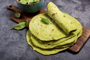 Green tortillas with spinach, tortilla flatbreads for wraps, trendy mexican food, healthy snack concept on dark background